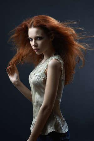 disdain: hermosa ni�a de cabello rojo en el fondo azul oscuro