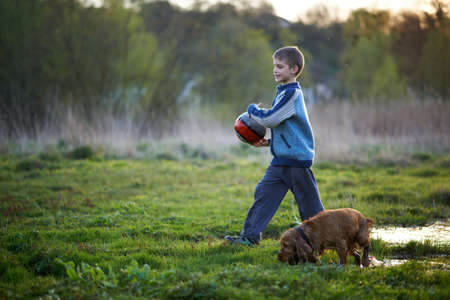 carying: boy with a ball walking with a dog on the lawn