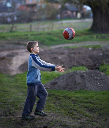 throws: boy in the countryside plays the ball in the evening Stock Photo