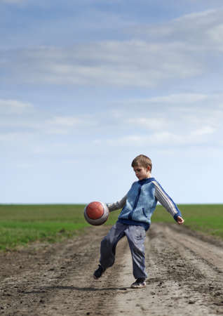 boy playing with a ball on the mud road photo