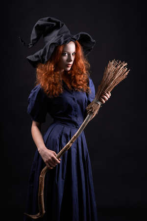sibyl: Young beautiful red-haired witch with a broom in the dark Stock Photo