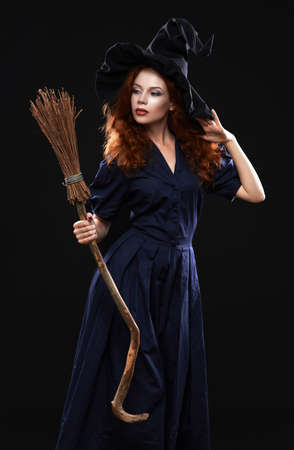 Young beautiful red-haired witch with a broom in the dark photo
