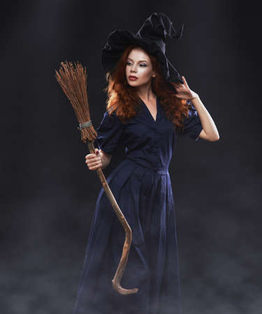 Young beautiful red-haired witch with a broom in the dark fog photo
