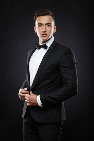 handsome business man in suit straightens his jacket on dark background photo