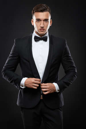 corrects: handsome business man in a suit straightens his jacket on dark background