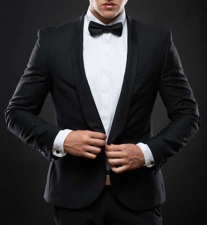handsome business man in suit on a dark background photo