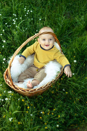 he laughs: small smiling child in a sweater sitting in a basket on the grass