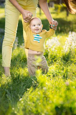 teaches: Mom teaches son walking grass on the lawn