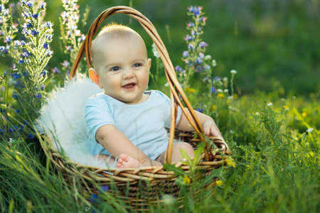 he laughs: small smiling child in sliders sitting a basket on the grass Stock Photo