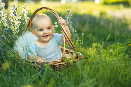 small smiling child in sliders sitting a basket on the grass Stock Photo