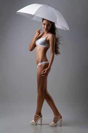 femme se deshabille: Dame �l�gante en lingerie avec un parapluie sur un fond gris