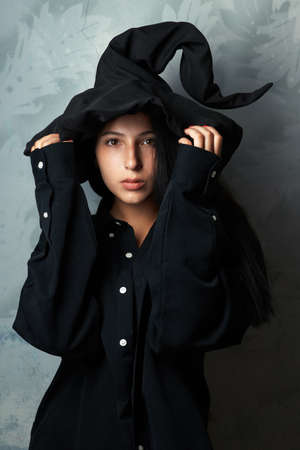 beautiful girl in a witch costume looks mysteriously photo