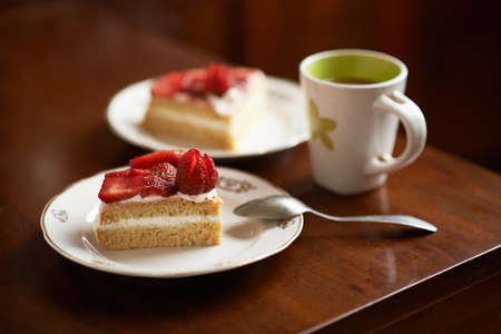 sponge cake decorated with strawberries cup of coffee photo