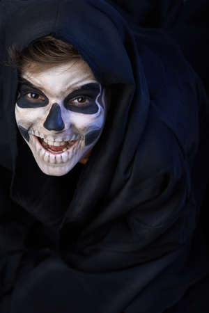 Teen with make-up of the skull in a black cloak laughs photo