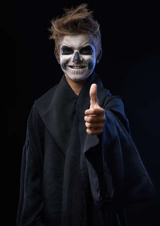 Teen with makeup skull cape showing thumbs up photo