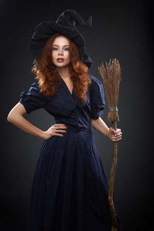 beautiful red-haired girl in a blue costume witch photo