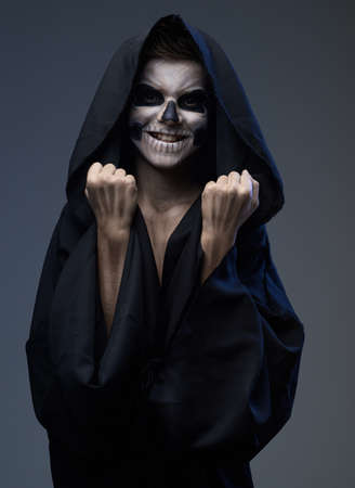 insidious: Teen with make-up of the skull in a black cloak showing his fists Stock Photo