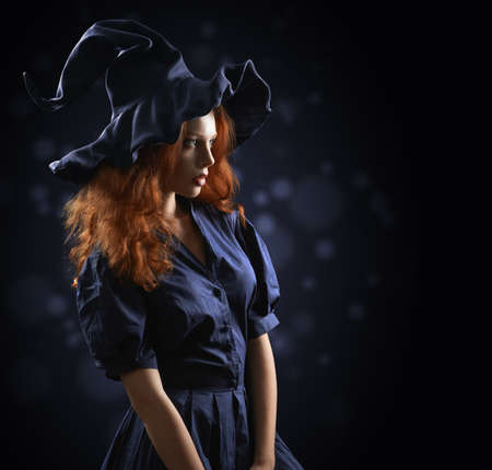 beautiful red-haired girl in a blue costume witch blurred background photo