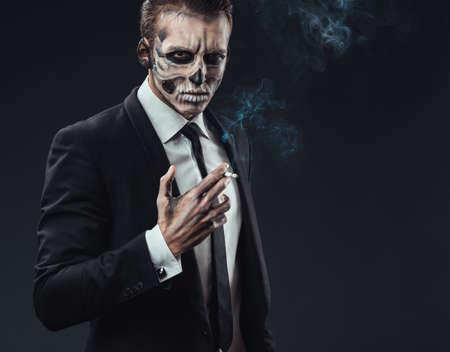 portrait businessman smoking with makeup skeleton photo