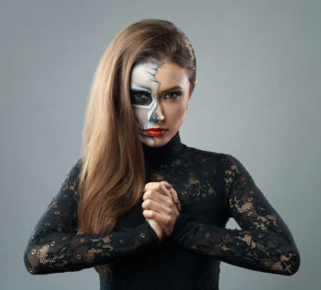 beautiful woman with make-up skeleton clasped hands photo