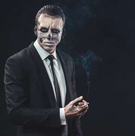 portrait of a businessman smoking with make-up skeleton photo