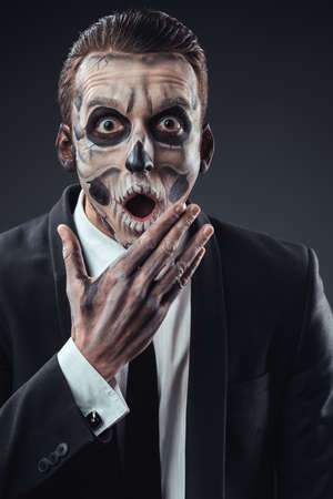 Surprised businessman with a make-up of the skeleton photo