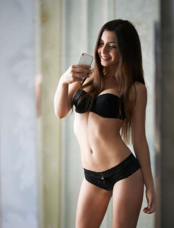 girl in lingerie makes a photo of yourself in the mirror