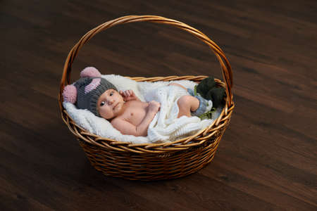 kids weaving: newborn baby in the cap in the basket on the floor Stock Photo