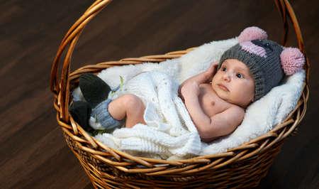 newborn baby in the cap in the basket on the floor Stock Photo