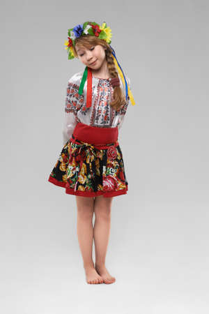 Pretty red-haired girl in the Slavic national costume shy photo