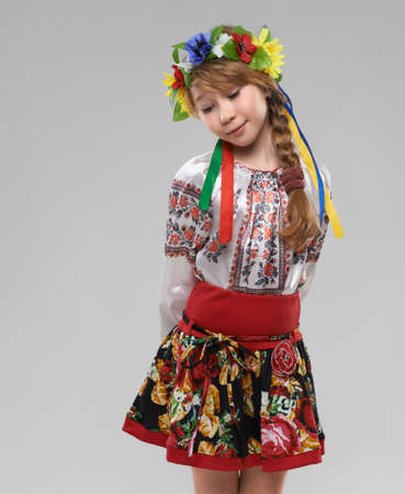 national costume: Pretty red-haired girl in the Slavic national costume shy