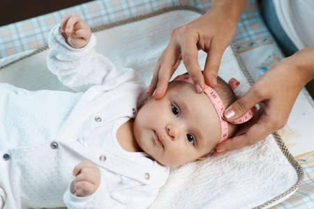 therapist measures the size of the head of a beautiful baby