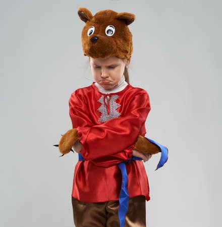 slavic: upset red-haired girl in costume of Slavic bear Stock Photo