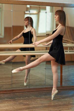 barre: beautiful girl practicing dance holding Barre