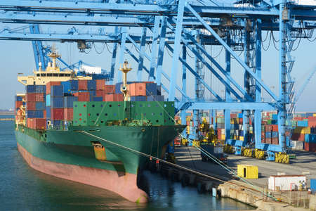 shipping port: Cranes load containers on a large transport ship