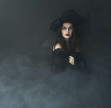 necromancer: slender witch in a smoke on a black background
