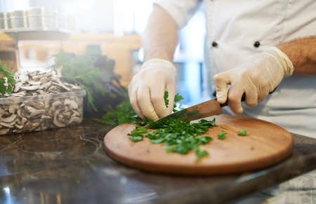 Chef wearing gloves cut greens