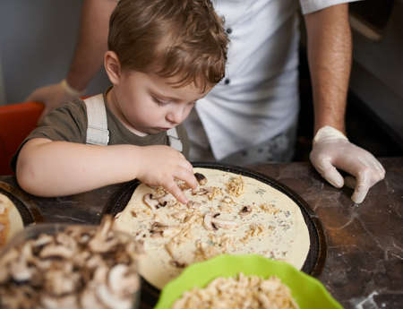 puts: boy puts the ingredients for pizza Stock Photo