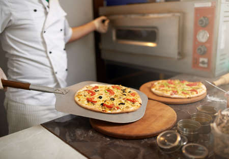 freshly prepared: chef puts on the table freshly prepared pizza Stock Photo