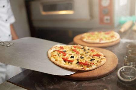 freshly prepared: chef puts on the board freshly prepared pizza