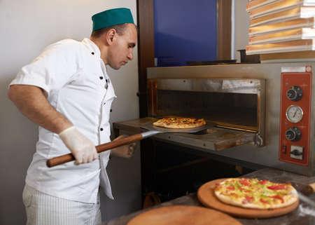 Cook nam de pizza uit de oven klaar Stockfoto