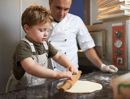 roll out: Boy learns to roll out the pizza dough