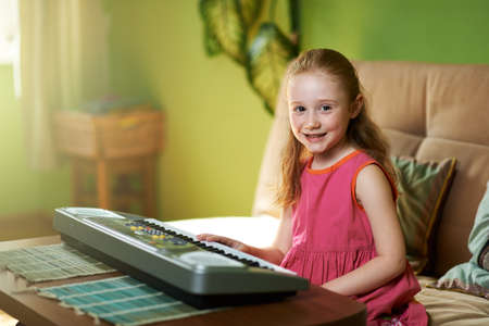 sits: cheerful girl sits near an electronic piano