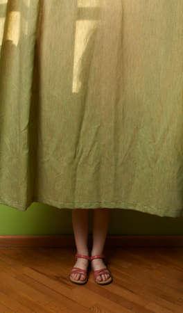 little girl feet: the little girl hid behind the curtain Stock Photo