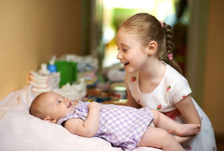 diaper changing table: older sister having fun talking to the younger