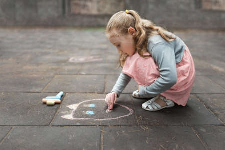 squatting: girl in a pink dress drawing with chalk on the pavement