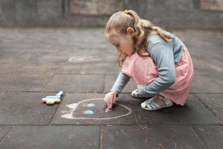 meisje in een roze jurk tekenen met krijt op de stoep