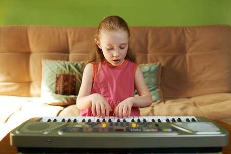 playing on divan: Girl singing while playing on an electronic keyboard