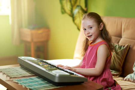 playing on divan: beautiful girl sings while playing on an electronic piano