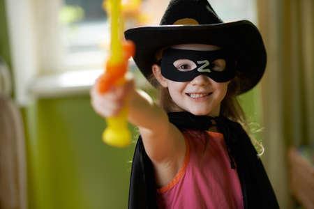raises: Pretty girl in a superhero suit raises his sword up